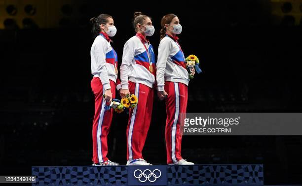 Gold medallist Russia's sabre team celebrate on podium during the medal ceremony for the womens team sabre during the Tokyo 2020 Olympic Games at the...