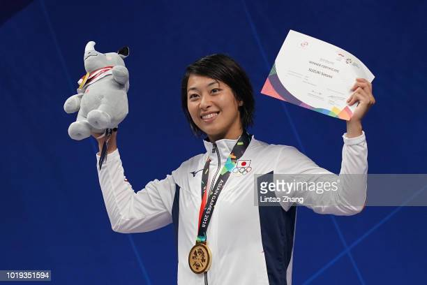 Gold medallist Satomi Suzuki of Japan celebrates during the victory ceremony of the women's 100m breaststroke swimming event on day one of the Asian...