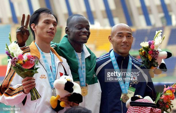 Gold medallist Saudi Arabian Salem al-Ahmadi poses on the podium with silver medalist Chinese Lao Jiangfeng and bronze Takashi Komatsu from Japan...