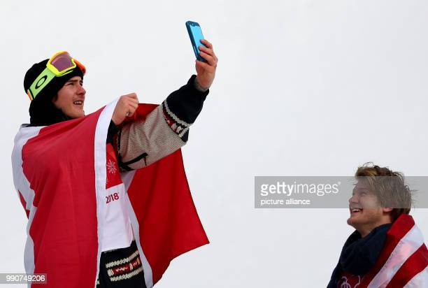 Gold medallist Sebastien Toutant from Canada celebrates his victory by taking a selfie next to Kyle Mack during the Snowboard Big Air finals in...