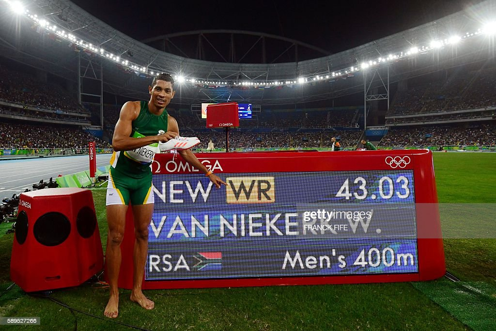 Gold medallist South Africa's Wayde van Niekerk points to his new world record displayed on a board after the Men's 400m Final during the athletics event at the Rio 2016 Olympic Games at the Olympic Stadium in Rio de Janeiro on August 14, 2016. / AFP / FRANCK