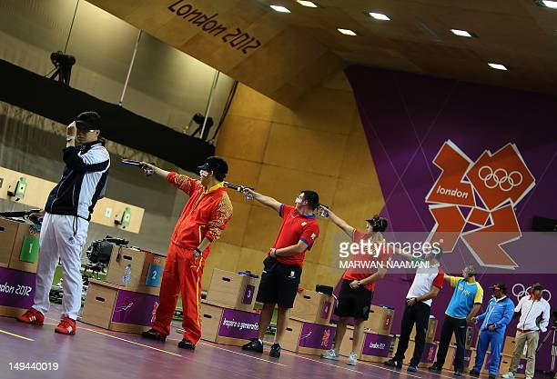 Gold medallist South Korean Jin Jongoh adjusts his hat as others compete the 10m Air Rifle men's final at the Royal Artillery Barracks in London on...