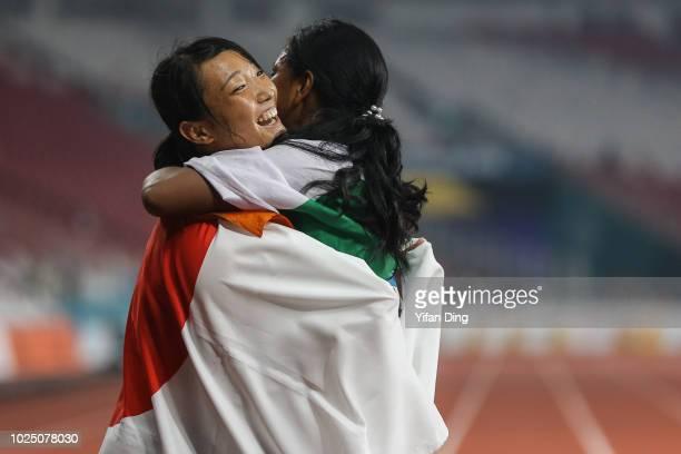 Gold medallist Swapna Barman of India celebrates with silver medallist Yamasaki Yuki of Japan during Athletics WomenÕs Heptathlon 800m at GBK Main...