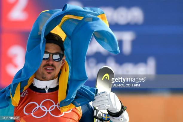 TOPSHOT Gold medallist Sweden's Andre Myhrer hold his national flag as he celebrates on the podium during the victory ceremony in the Men's Slalom at...