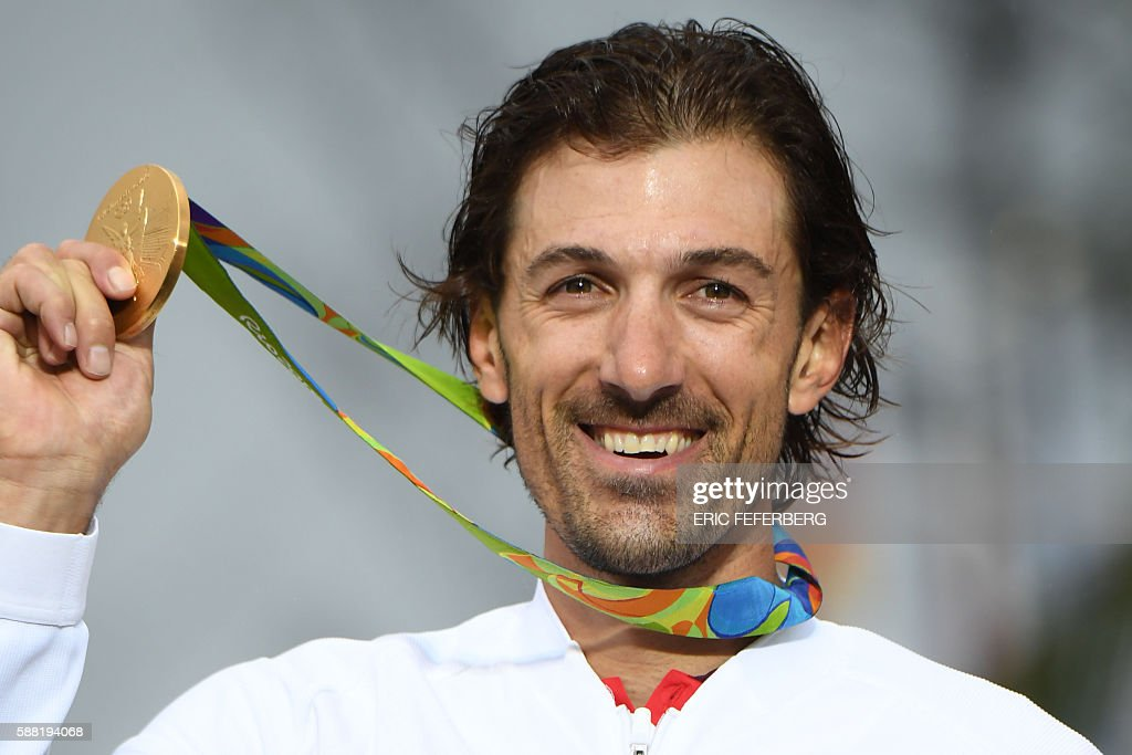 Gold medallist Switzerland's Fabian Cancellara poses on the podium after the Men's Individual Time Trial event at the Rio 2016 Olympic Games in Rio de Janeiro on August 10, 2016. / AFP / Eric FEFERBERG