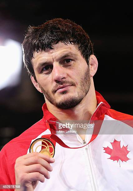 Gold medallist Tamerlan Tagziev of Canada poses during the medal ceremony for the Men's FS 86 kg at Scottish Exhibition and Conference Centre during...