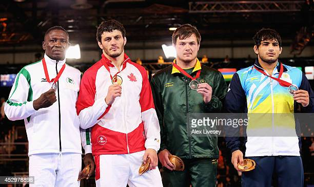Gold medallist Tamerlan Tagziev of Canada poses with silver medallist Andrew Dick of Nigeria and bronze medallists Armando Hietbrink of South Africa...