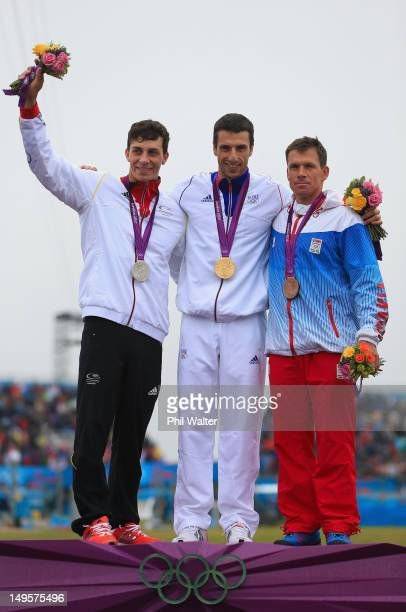 Gold medallist Tony Estanguet of France celebrates with silver medallist Sideris Tasiadis of Germany and bronze medallist Michal Martikan of Slovakia...
