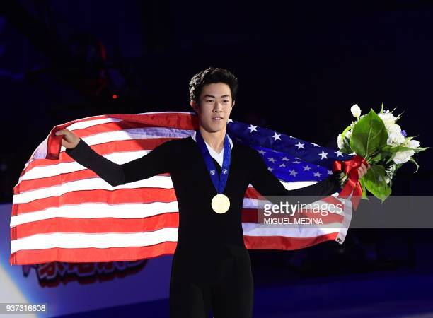 Gold medallist US Nathan Chen poses with a US flag on the podium of the MenFree Skate program at the Milan World Figure Skating Championship 2018 on...