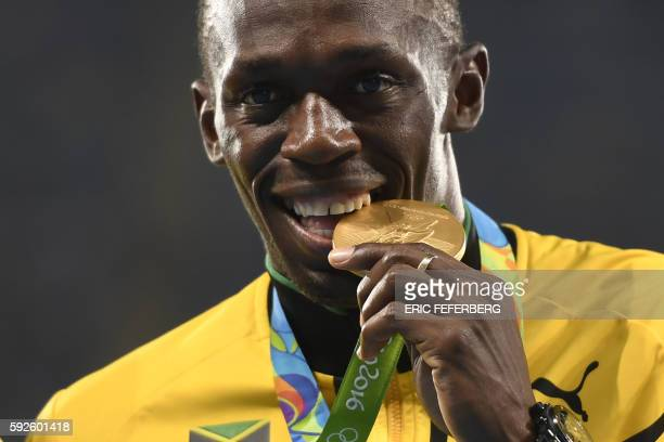 TOPSHOT Gold medallist Usain Bolt stands on the podium during the medal ceremony for the Men's 4x100m final during the athletics at the Rio 2016...