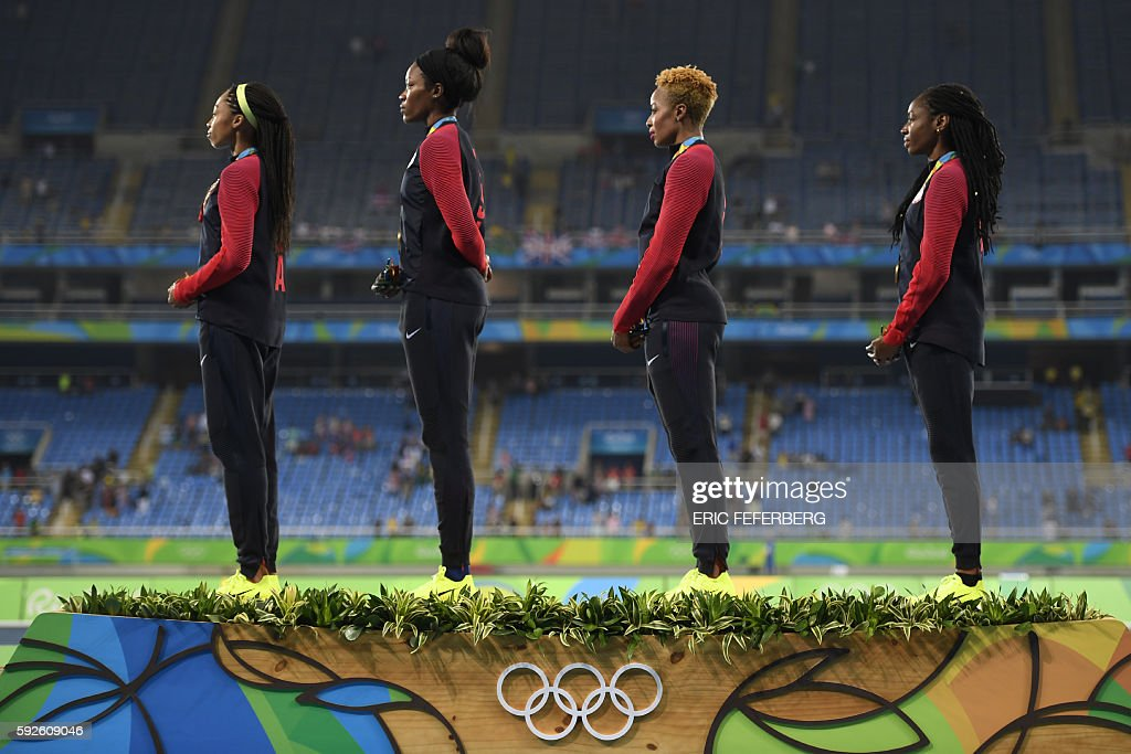 Gold medallist USA's Allyson Felix, USA's Phyllis Francis, USA's Natasha Hastings and USA's Courtney Okolo listen to their national anthem as they stand on the podium of the Women's 4x400m Relay Final during the athletics event at the Rio 2016 Olympic Games at the Olympic Stadium in Rio de Janeiro on August 20, 2016. / AFP / Eric FEFERBERG
