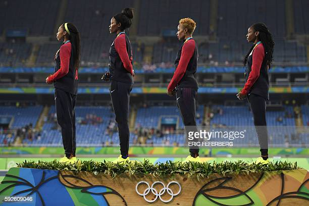 Gold medallist USA's Allyson Felix USA's Phyllis Francis USA's Natasha Hastings and USA's Courtney Okolo listen to their national anthem as they...