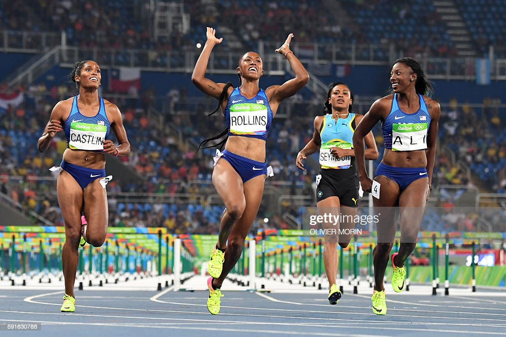 Gold medallist USA's Brianna Rollins (2ndL) celebrates as she crosses the finish line ahead of silver medallist USA's Nia Ali (R) and bronze medallist USA's Kristi Castlin (L) to win the Women's 100m Hurdles Final during the athletics event at the Rio 2016 Olympic Games at the Olympic Stadium in Rio de Janeiro on August 17, 2016. / AFP / OLIVIER