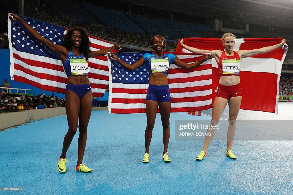 Gold medallist USA's Dalilah Muhammad (C) celebrates with silver medallist Denmark's Sara Slott Petersen (R) and bronze medallist USA's Ashley Spencer after the Women's 400m Hurdles Final during the athletics event at the Rio 2016 Olympic Games at the Olympic Stadium in Rio de Janeiro on August 18, 2016. / AFP / Adrian DENNIS