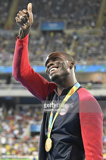 Gold medallist USA's Kerron Clement gives the thumb up on the podium of the Men's 400m Hurdles during the athletics event at the Rio 2016 Olympic...