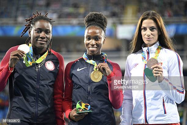 Gold medallist USA's Tianna Bartoletta poses with silver medallist USA's Brittney Reese and bronze medallist Serbia's Ivana Spanovic on the podium of...