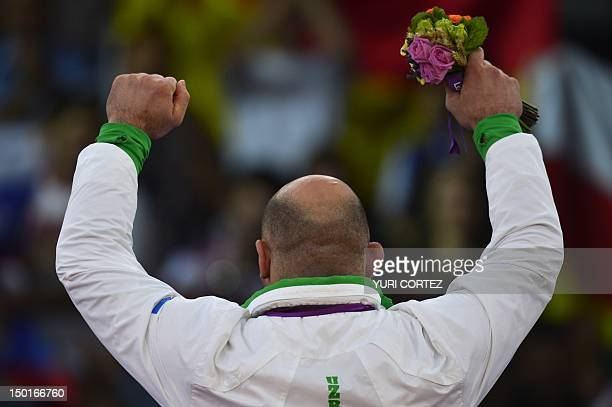 Gold medallist Uzbekistan's Artur Taymazov celebrates on the podium of the Men's 120kg on August 11 2012 during the wrestling event of the London...