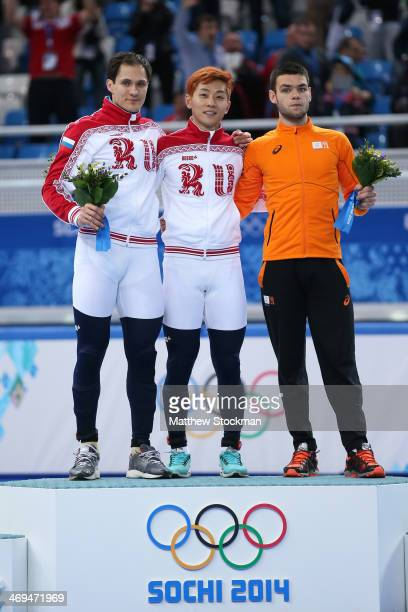 Gold medallist Victor An of Russia stands on the podium during the flower ceremony with silver medallist Vladimir Grigorev of Russia and bronze...