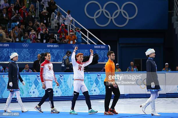 Gold medallist Victor An of Russia walks out for the flower ceremony with silver medallist Vladimir Grigorev of Russia and bronze medallist Sjinkie...