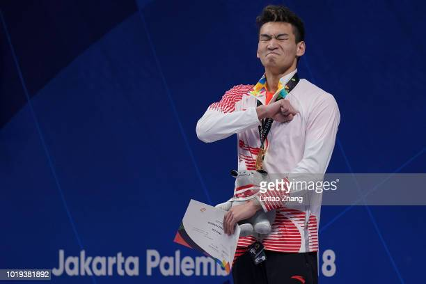 Gold medallist Xu Jiayu of China celebrates during the victory ceremony of the men's 100m backstroke swimming event on day one of the Asian Games on...