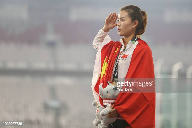 Gold medallist Yang Jiayu of China salutes to Chinese flag during Athletics WomenÕs 20km Race Walk medal ceremony at GBK Main Stadium on day eleven...