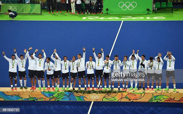 Gold medallists Argentina's players celebrate on the podium during the men's field hockey medals ceremony of the Rio 2016 Olympics Games at the...