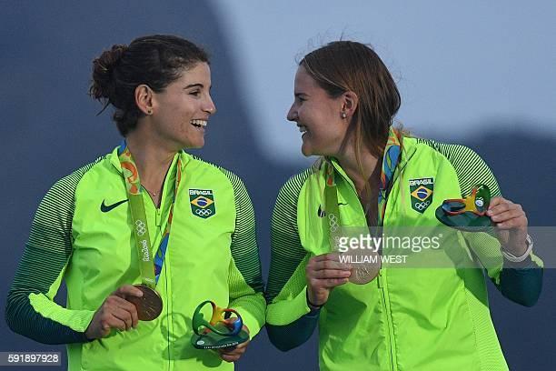 Gold medallists Brazil's Martine Grael and Brazil's Kahena Kunze celebrate on the podium of the 49er FX Women medal race at Marina da Gloria during...