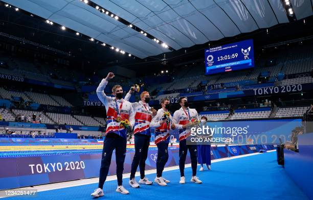 Gold medallists Britain's Duncan Scott, Britain's Tom Dean, Britain's Matthew Richards and Britain's James Guy pose after the final of the men's...