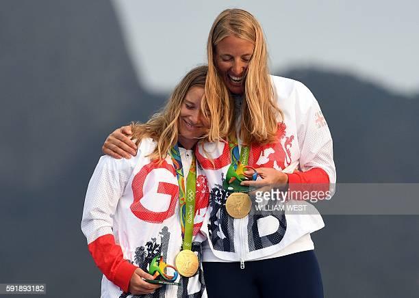 Gold medallists Britain's Hannah Mills and Saskia Clark celebrate on the podium of the 470 Women medal race at Marina da Gloria during the Rio 2016...