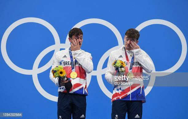 Gold medallists Britain's Thomas Daley and Britain's Matty Lee wipe their eyes as they pose with their medals after wining the men's synchronised 10m...