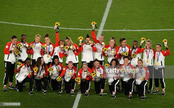 Gold medallists Canada's team pose the medals during the victory ceremony after the Tokyo 2020 Olympic Games women's final football match at the...