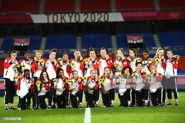 Gold medallists Canada's team pose with the medals during the victory ceremony after the Tokyo 2020 Olympic Games women's final football match at the...