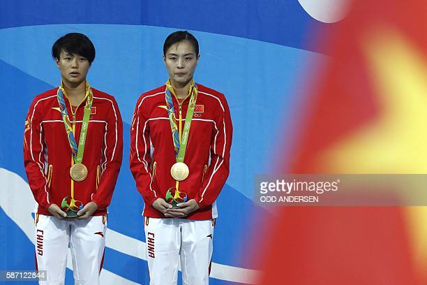 Gold medallists China's Wu Minxia and Shi Tingmao listen to their national anthem during the podium ceremony of the Women's Synchronized 3m...