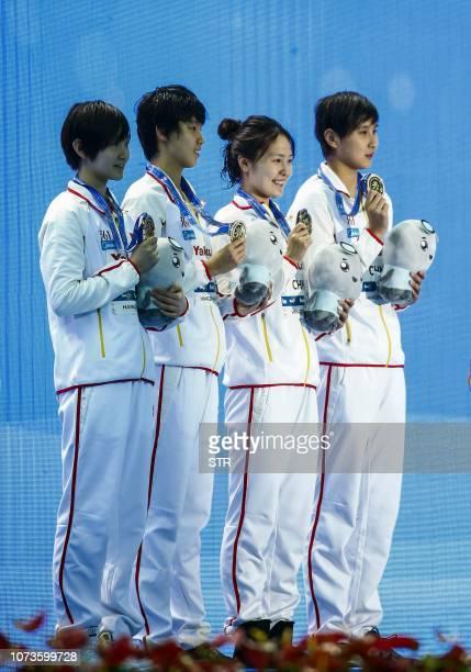 Gold medallists Chinese swimmers Li Bingjie Yang Junxuan Zhang Yuhan and Wang Jianjiahe pose on the podium after the women's 4x200m freestyle relay...