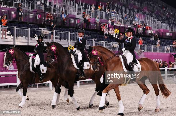 Gold medallists Dorothee Schneider of Germany, Isabell Werth of Germany and Jessica von Bredow-Werndl of Germany wave as they ride together with...