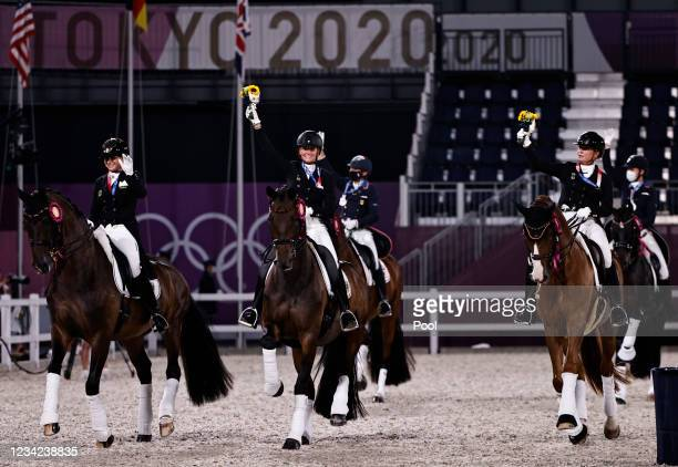 Gold medallists Dorothee Schneider of Germany, Isabell Werth of Germany and Jessica von Bredow-Werndl of Germany ride together with other medallists...