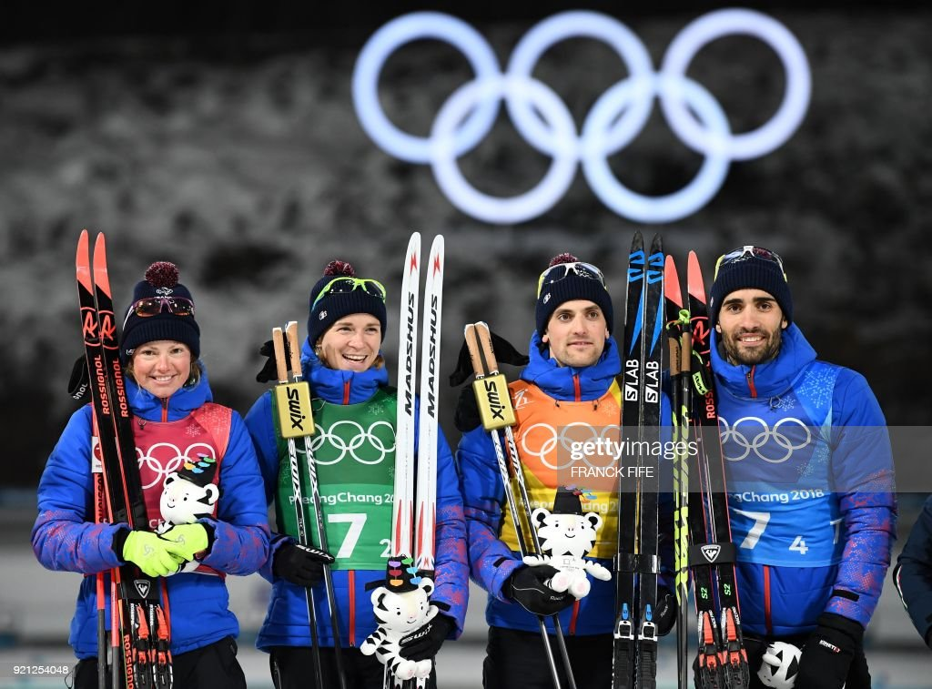 TOPSHOT - (From L) Gold medallists France's Marie Dorin Habert, France's Anais Bescond, France's Simon Desthieux, and France's Martin Fourcade celebrate on the podium during the victory ceremony in the mixed relay biathlon event during the Pyeongchang 2018 Winter Olympic Games on February 20, 2018, in Pyeongchang. /