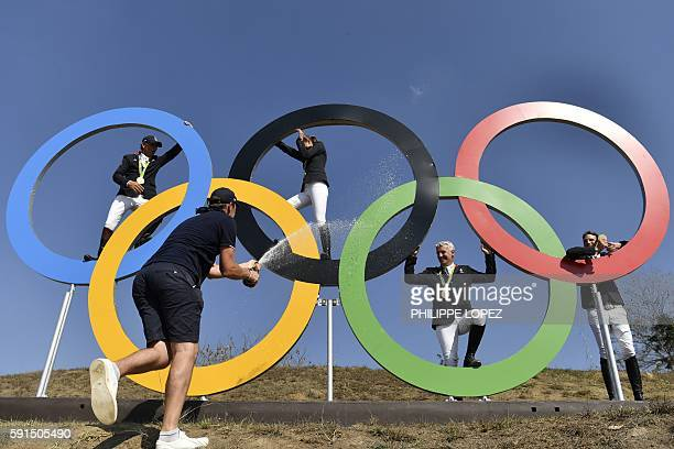 Gold medallists, France's riders Philippe Rozier , Roger Yves Bost , Penelope Leprevost and Kevin Staut, celebrate as they pose with the Olympic...