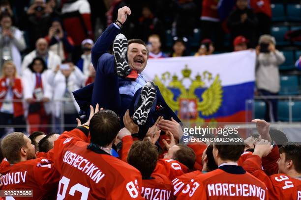 TOPSHOT Gold medallists from the Olympic Athletes from Russia carry their head coach Oleg Znarok after the medal ceremony after the men's gold medal...