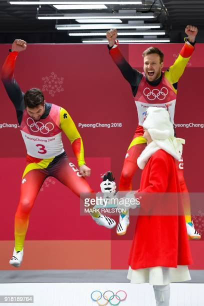 Gold medallists Germany's Tobias Wendl and Tobias Arlt celebrate on the podium during the victory ceremony after the doubles luge final event during...