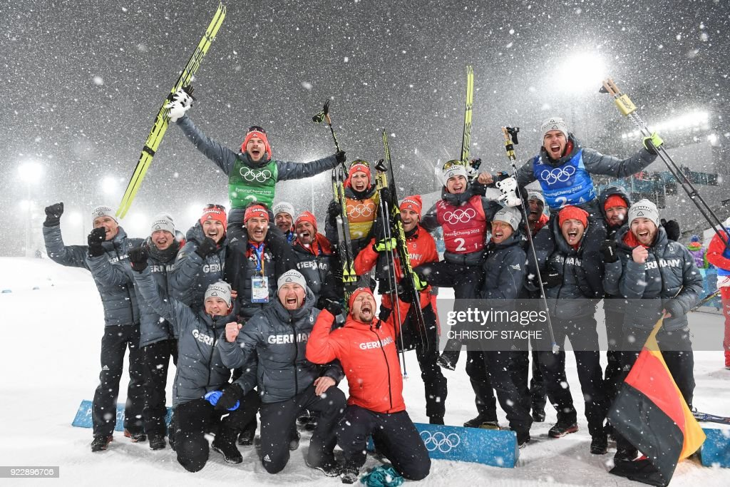 TOPSHOT - Gold medallists Germany's Vinzenz Geiger, Germany's Fabian Riessle, Germany's Eric Frenzel and Germany's Johannes Rydzek celebrate with the team members during the victory ceremony for the nordic combined team Gundersen LH/4x5km event at the Alpensia Cross-Country Skiing Centre during the Pyeongchang 2018 Winter Olympic Games on February 22, 2018 in Pyeongchang. / AFP PHOTO / Christof STACHE