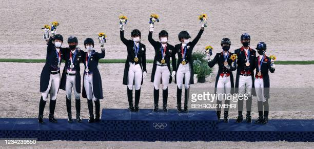Gold medallists of team Germany , silver medallists of the US team and Britain's Bronze medallists pose on the podium of the dressage grand prix...