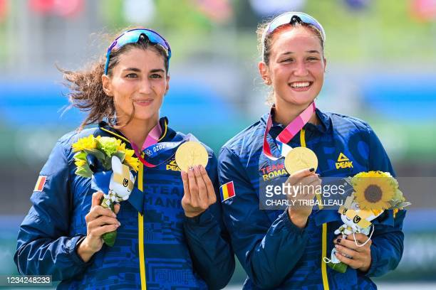 Gold medallists Romania's Ancuta Bodnar and Simona Radis celebrate on the podium following the women's double sculls final during the Tokyo 2020...