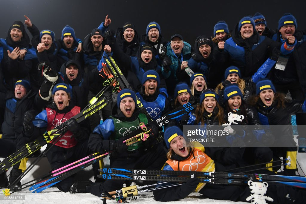 TOPSHOT - Gold medallists Sweden's Peppe Femling , Sweden's Jesper Nelin Sweden's Fredrik Lindstroem and Sweden's Sebastian Samuelsson (front ) celebrate with team members follwoing the victory ceremony in the men's 4x7,5km biathlon event during the Pyeongchang 2018 Winter Olympic Games on February 23, 2018, in Pyeongchang. /