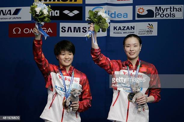 Gold medallists Tingmao Shi and Minxia Wu of China celebrate during the medal ceremony for the Women's 3m Springboard Synchronised Diving Final on...