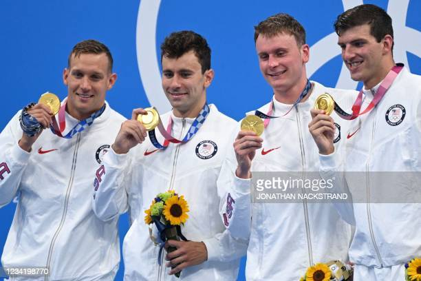 Gold medallists USA's Caeleb Dressel, USA's Blake Pieroni, Bowen Becker and USA's Zach Apple pose with their medals on the podium after the final of...