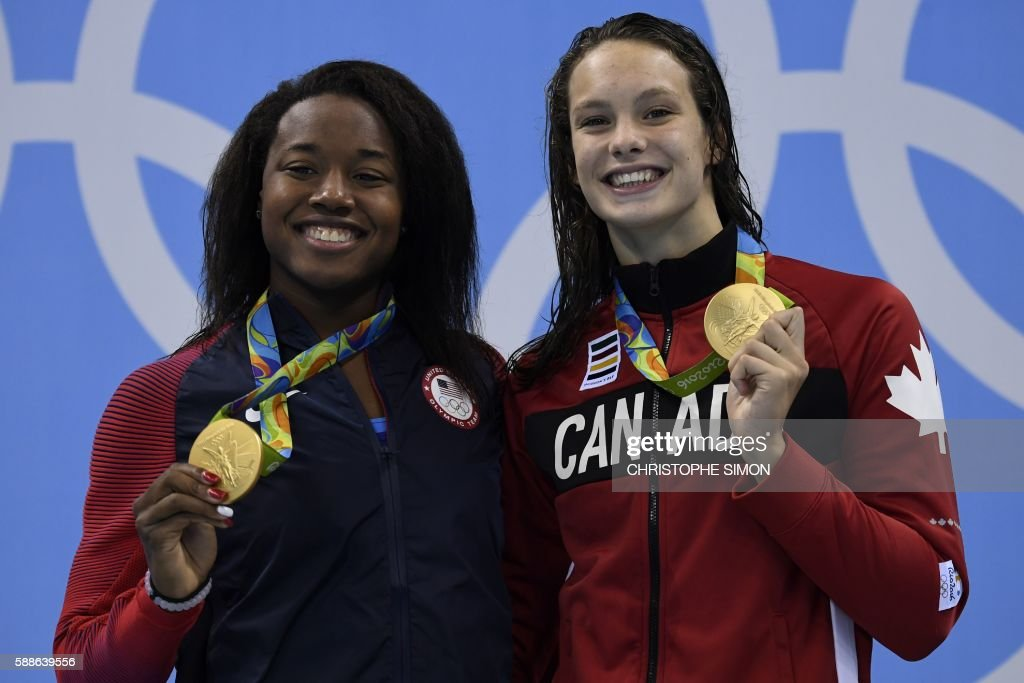 Gold medallists USA's Simone Manuel (L) and Canada's Penny Oleksiak pose on the podium of the Women's 100m Freestyle Final during the swimming event at the Rio 2016 Olympic Games at the Olympic Aquatics Stadium in Rio de Janeiro on August 11, 2016. /