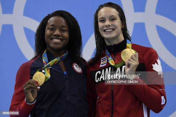 Gold medallists USA's Simone Manuel and Canada's Penny Oleksiak pose on the podium of the Women's 100m Freestyle Final during the swimming event at...
