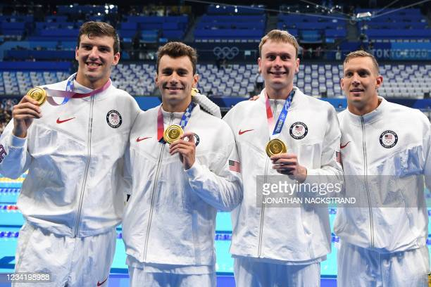 Gold medallists USA's Zach Apple, USA's Blake Pieroni, Bowen Becker and USA's Caeleb Dressel, pose with their medals as they leave the pool after the...