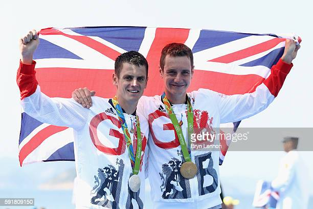 Gold medaltist Alistair Brownlee and silver medalist Jonathan Brownlee of Great Britain celebrate on the podium during the Men's Triathlon at Fort...